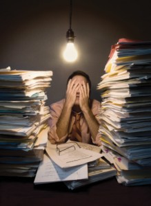 Businessman with stacks of paperwork, covering eyes