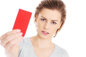 A picture of a serious woman showing a red card over white background