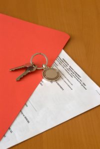 Red folder and keys with rental agreement.