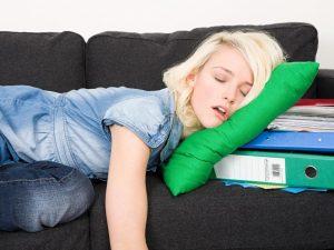 Une jeune femme dort sur une pile de dossiers
