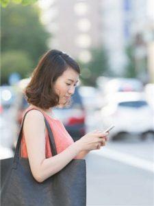 une femme utilise son smartphone dans la rue