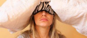 femme fatiguée avec oreiller sur la tête et masque sur les yeux