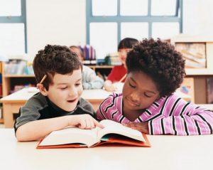 deux enfants lisent un livre ensemble dans une classe