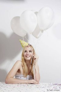 une jeune femme attend avec impatience, sourire, chapeau de fête et ballons