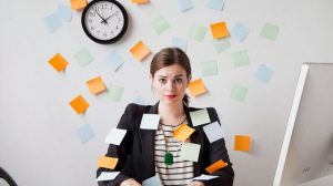 Femme au bureau recouverte de post-its, burn out