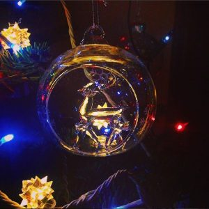 sapin de Noël, boule en verre avec un renne et guirlandes lumineuses