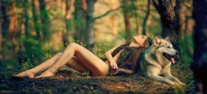 une femme nue dans la forêt adossée à un loup, femme sauvage et libre, liberté sexuelle