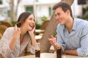 Un jeune couple flirte en buvant un verre en terrasse