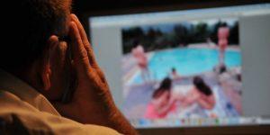 Un homme regarde des photos de jeunes femmes sur un ordinateur