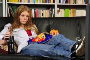 Une jeune femme s'ennuie devant la télé et grignote des chips