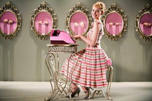 Femme tape sur une machine à écrire rose